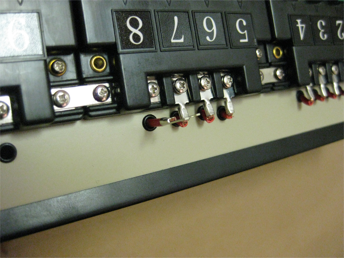 Power leads attached to Atlas selectors with terminal connectors on a model railroad control panel