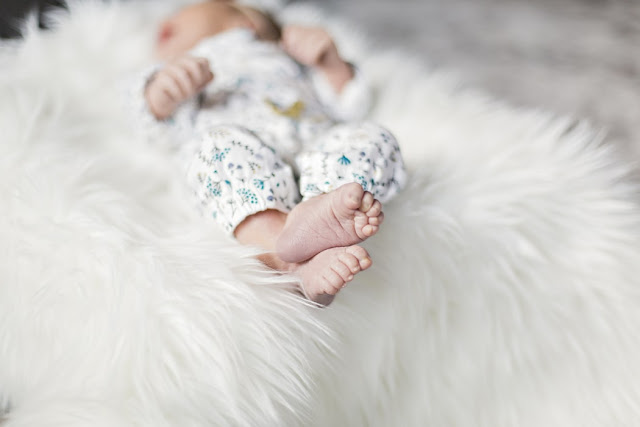Baby laying on a rug in a white and blue outfit, shot is mostly of their cute little feet