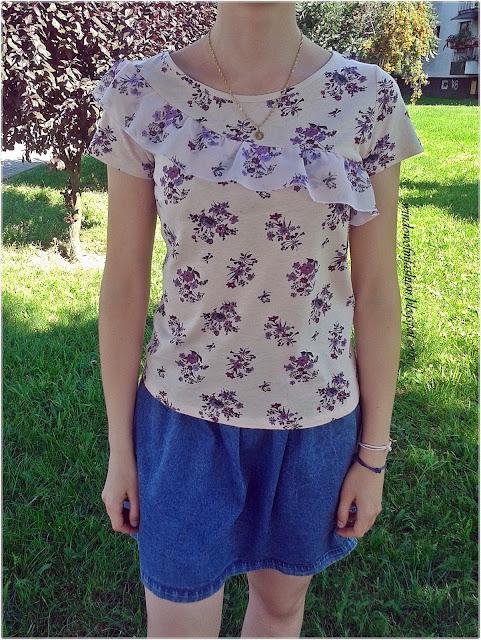 T-shirt z kwiatowym motywem i asymetryczną falbanką, jeansowa spódniczka, bransoletki z konikiem morskim oraz sterem, złoty medalik
