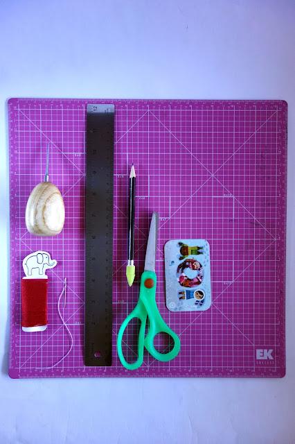awl, needle and thread, self-healing mat, ruler, scissors, pencil, bone folder, craft materials
