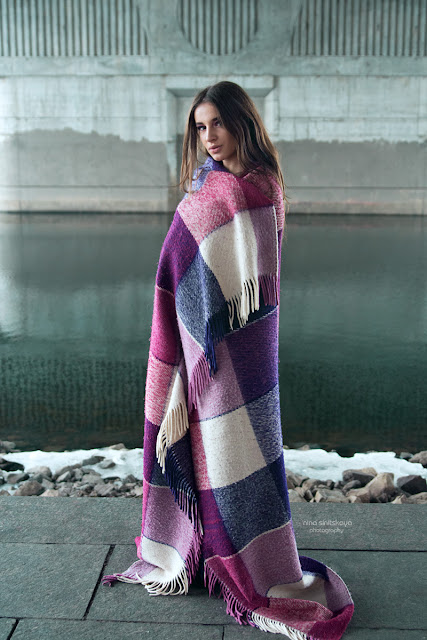 young woman covered in warm purple blanket