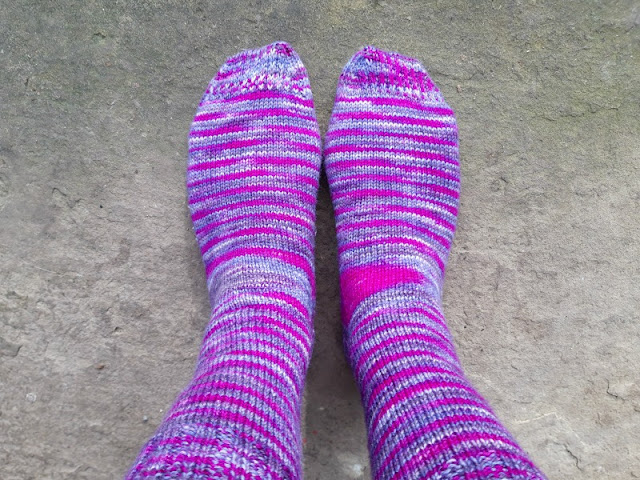 I'm standing on a stone paving flag wearing a pair of hand knitted socks in purple and pink stripy yarn