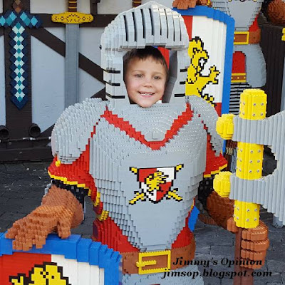 Grandson Benjamin posing behind and with his face through a Lego prop in the form of a knight.