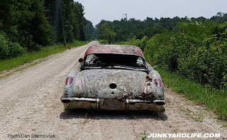 Rear shot of 1959 Corvette on dirt road.