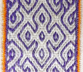 A close up photo of a textured white and purple tablet woven band with orange edges, patterned with a four leaf clover shape in the middle and twisted knot motifs on either side