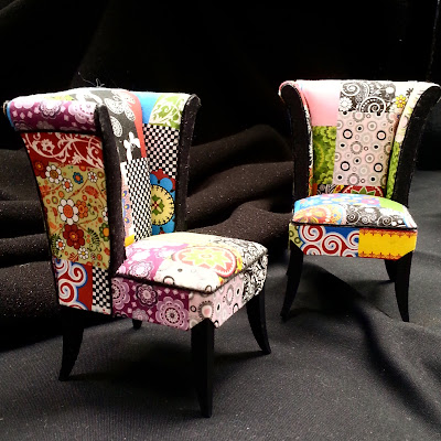 Two one-twelfth scale miniature modern armchairs, covered in a patchwork of bright fabrics.
