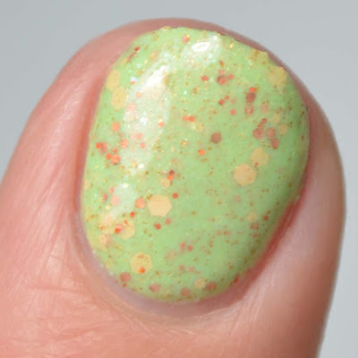 green nail polish with warm toned glitters swatch