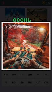 из кузова машины где сидят с кофе в руках наблюдают наступление осени