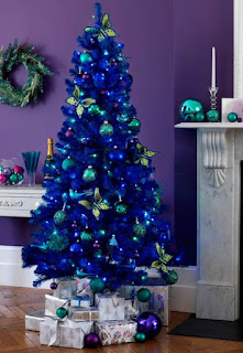 A blue Christmas tree with green ornaments and white packages beneath it