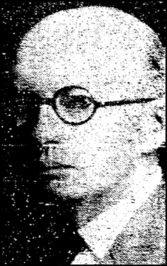 A bald, middle-aged white man wearing round, black-rimmed eyeglasses