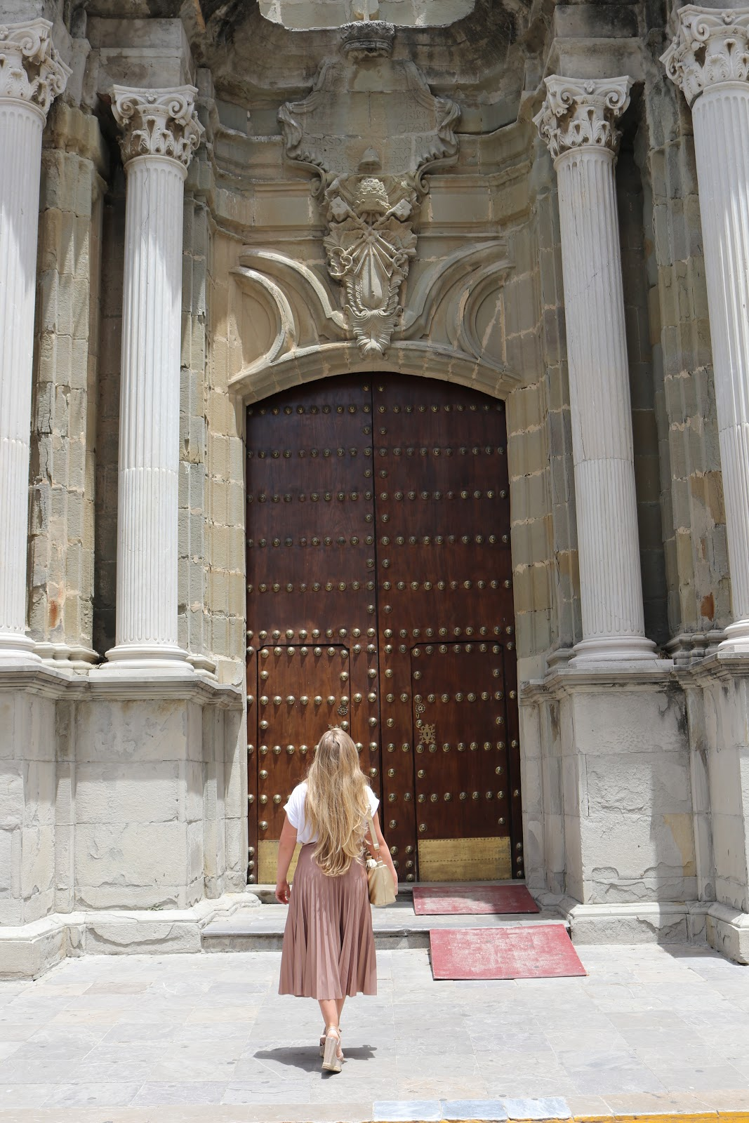 Blonde girl wearing metallic skirt looking up at Church Doors in Tarifa, Spain