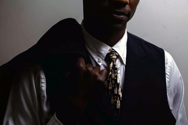 un hombre negro utilizando un traje y corbata