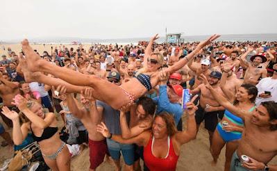 Juara wanita berulang Annie Seawright-Newton diangkat ke udara setelah memenangkan kompetisi tahunan Hermosa Beach Ironman ke-47 di mana para peserta harus berlari satu mil, mendayung papan selancar satu mil, dan menenggak enam bungkus bir pada 4 Juli 2021 di Pantai Hermosa , California. AFP