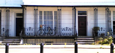 Bicycle behind railings of elegant Regency buidling