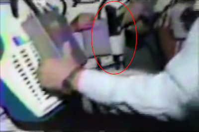 Still frame from video showing hand on holstered light gun. Another suit is being prepared in the foreground