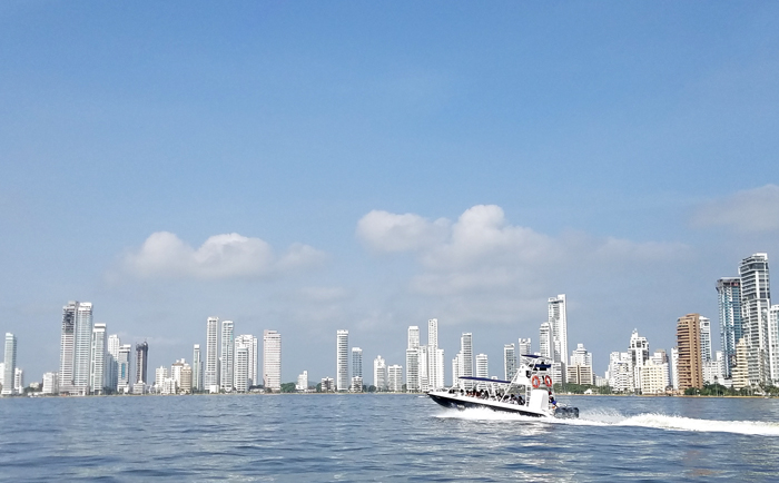 boat travaling alongside Cartagena's coast line with the tall buildings in the distance.