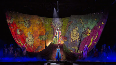 ID: a human person walking onto a stage. The stage is painted and their costume is designed in such a way that it looks like one garment spreads out across the entire stage in several colors.
