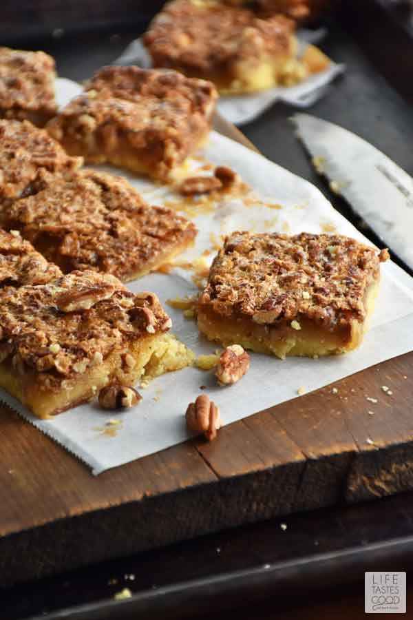 Pecan Pie Bars cut into squares and served on a rustic wood cutting board