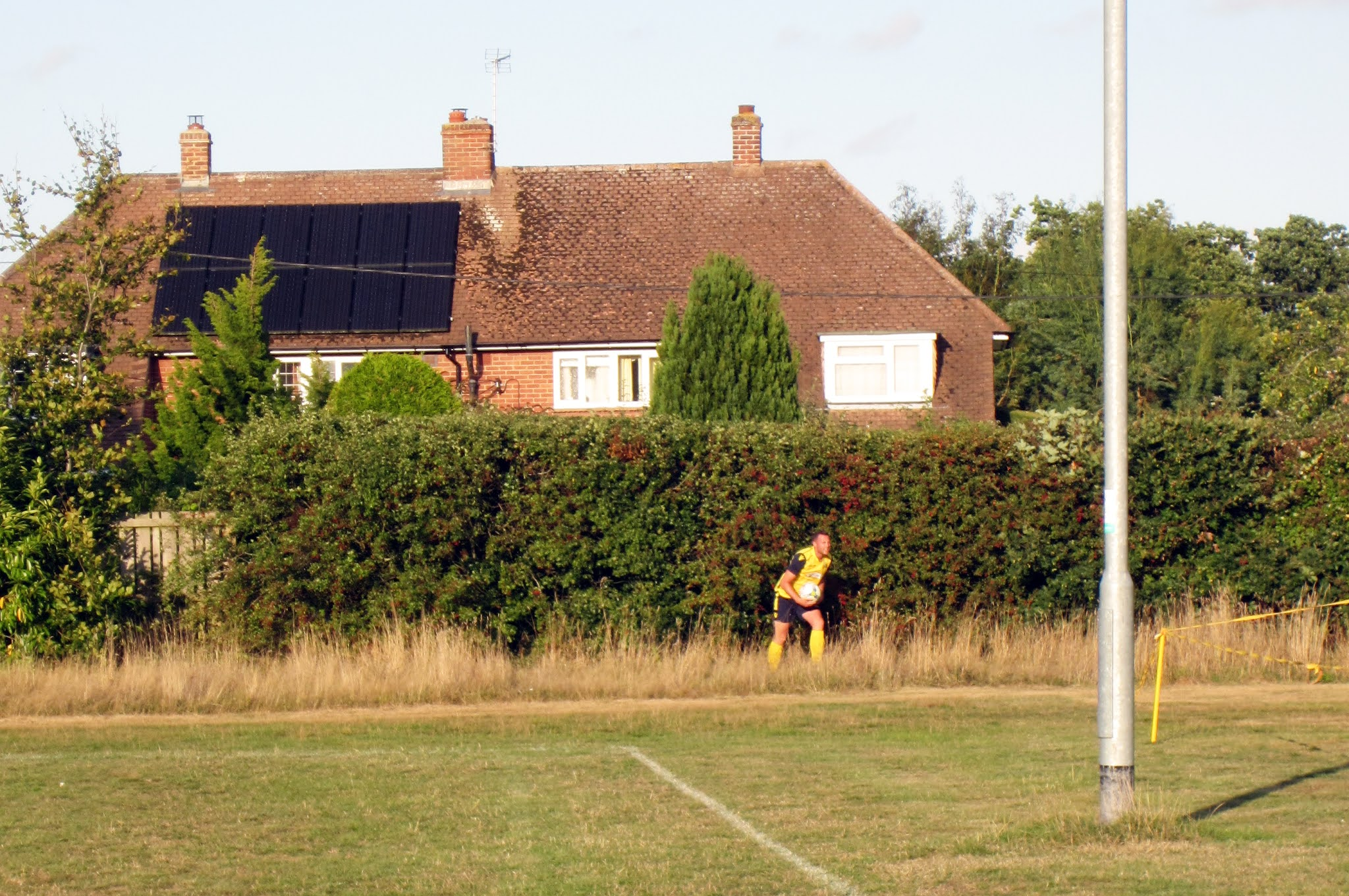 A Mortimer FC player retrieves the ball from the hedge