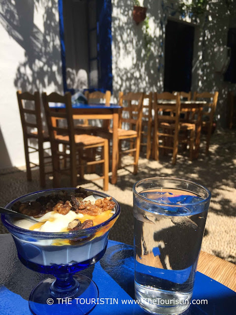 A glass of water and a glass with yogurt, honey and walnuts on a blue table in a cafe with a cobbled floor.
