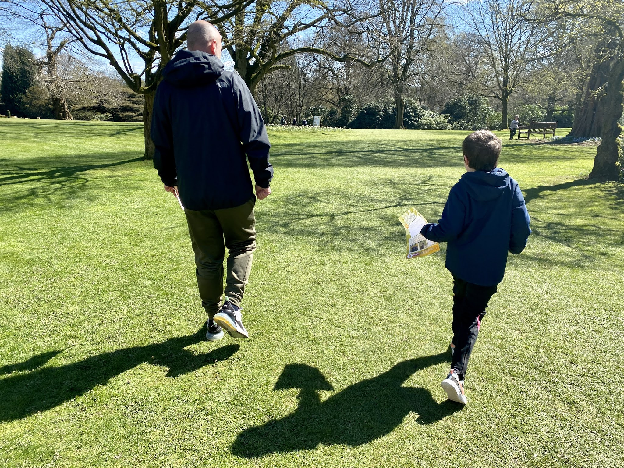 Dad and son walking along the grass