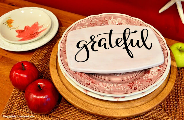 Grateful Sticker on white painted board on a cake plate with fall plates around it