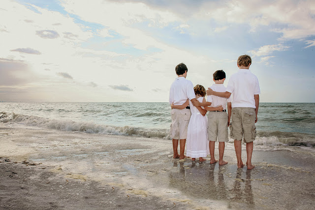 four children looking out at the sunset on sanibel