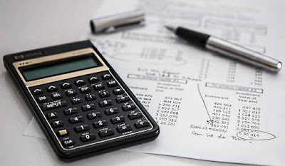 Calculator and pen being used to do a budget.