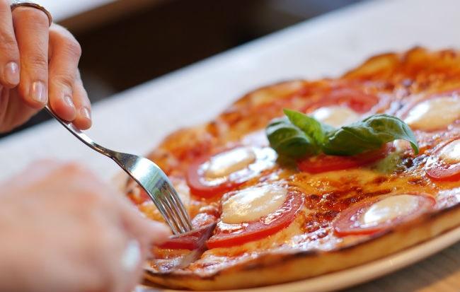 Mani che impugnano coltello e forchetta per tagliare una pizza su un piatto bianco