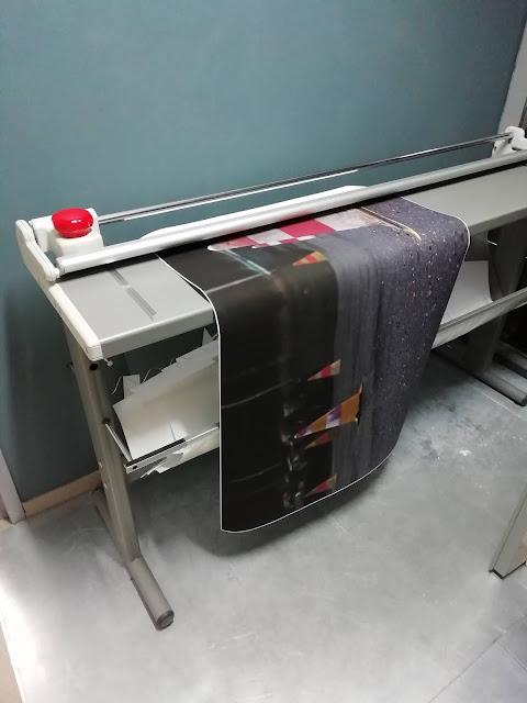 Kuvassa leikataan paperin valkoisia reunoja pois kuvan ympäriltä