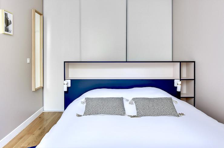 Dormitorio con armario detrás del cabecero de la cama.