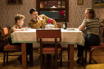 Scarlett Johansson, Roman Griffin Davis, and Taika Waititi as Adolf Hitler sit at the kitchen table together in a Jojo Rabbit movie still