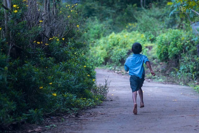 A tribal school boy running in a village of Munnar, Kerala