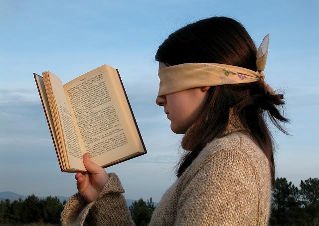 kobieta czytająca książkę z zawiązanymi oczami