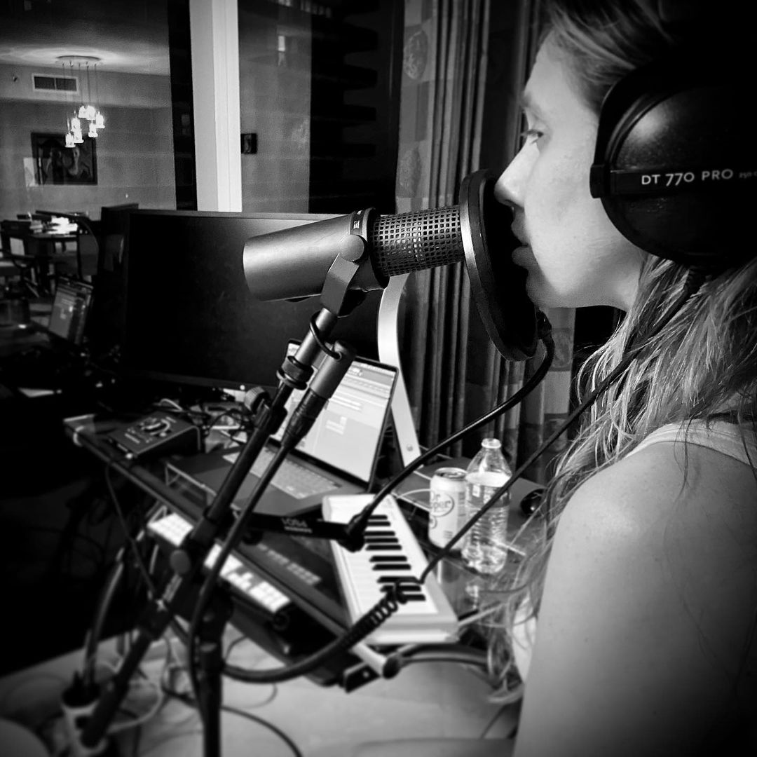 Black and white photo of Suzie in the recording studio wearing headphones and a microphone in front of her
