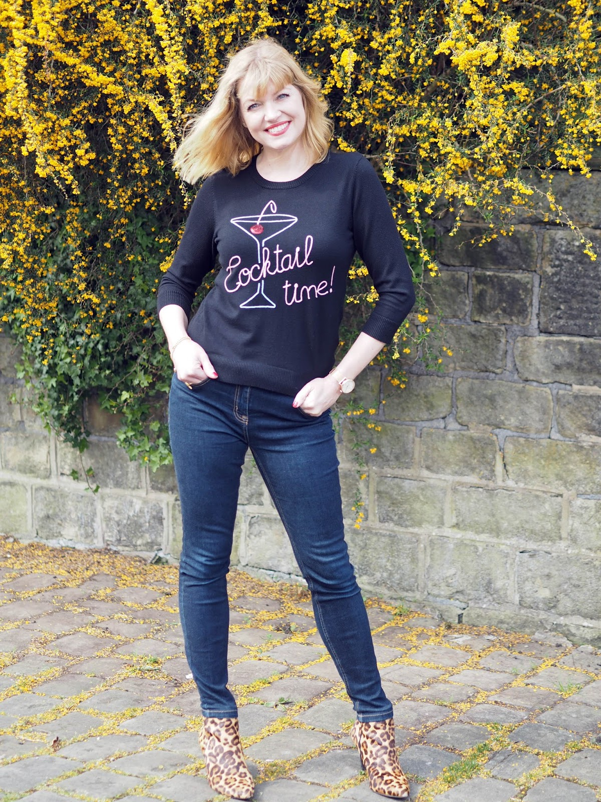 40 plus style blogger What Lizzy Loves wears What Lizzy Loves. Cocktail glass logo top worn with skinny jeans and high-heeled leopard print boots