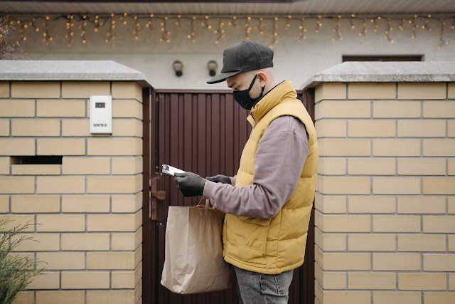 A masked up delivery person delivering a package to a home.