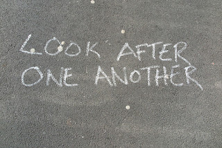 "Chalk hand-lettering, reads ""LOOK AFTER ONE ANOTHER"""