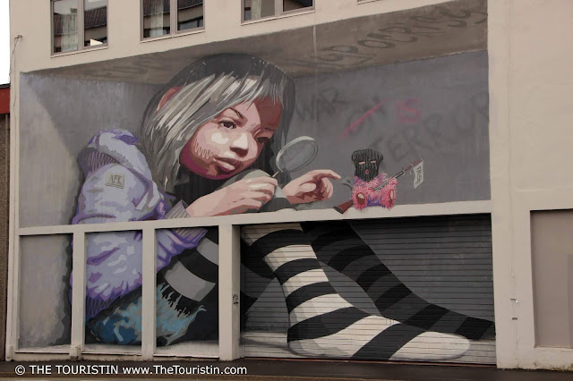 Street Art Mural of a girl in a lilac jacket and striped socks holding a magnifying glass by artist AFK in Bergen in Norway.