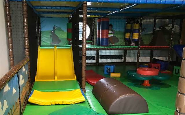 The soft play area for age 3 and under showing a small yellow slide a small raised area and lots of cushioned areas