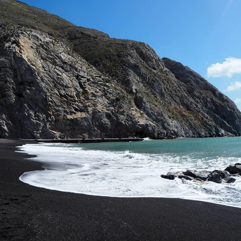 The incredible black sand beach attracts check-in visitors in Greece