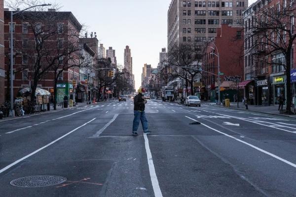 Một người đàn ông đeo mặt nạ bảo vệ đi bộ trên đường phố Manhattan. Ảnh: The Washington Post