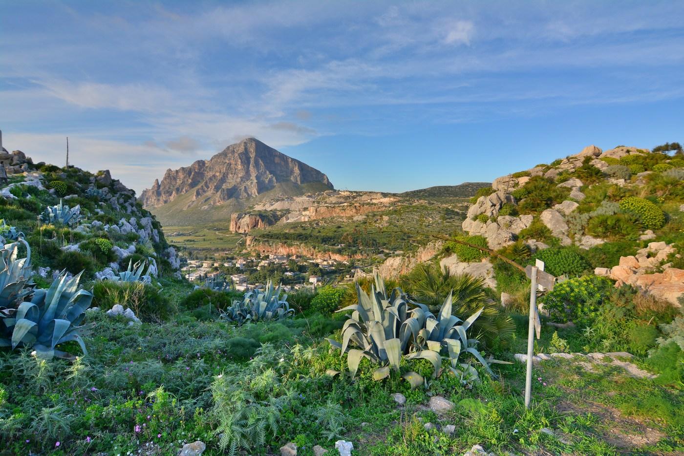 On aperçoit au loin, dans la falaise ocre dans l'axe du Monte Cofano, l'ouverture de la grotte.