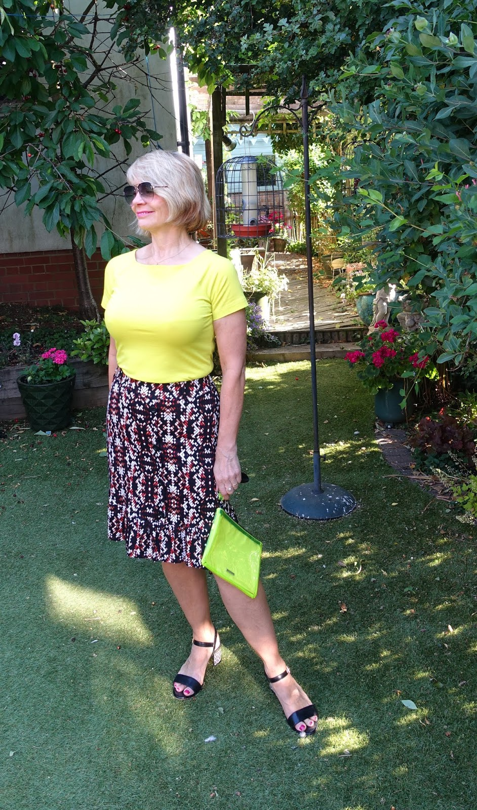 Gail Hanlon from Is This Mutton the over 50s style blog in brown and black geometric skirt worn with acid yellow top and black crystal heeled sandals