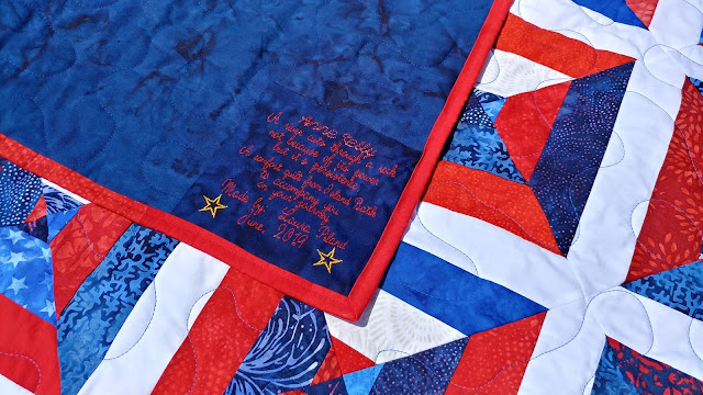 Red, white, and blue batik string quilt with embroidered label