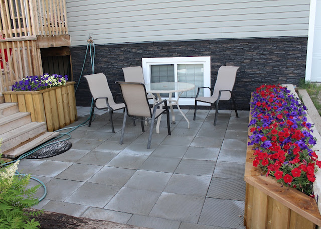 Patio, planters filled with petunias, patio furniture