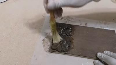 تطبيق سيلر على قطعة مصبوغة من عجينة الخشب على شكل وردة