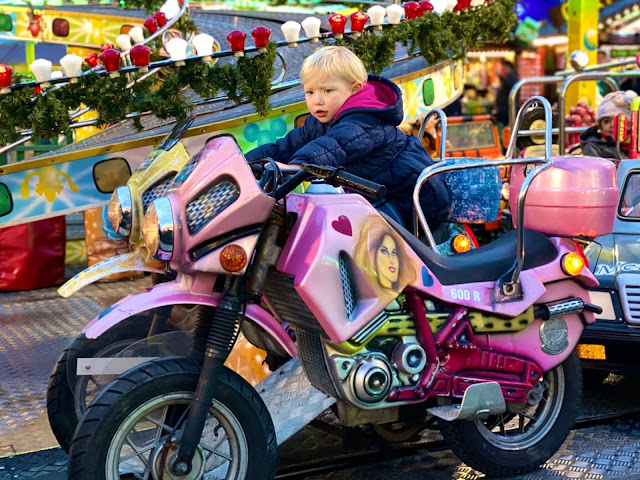 A 3 year old child on a bike on a ride while visiting winter wonderland