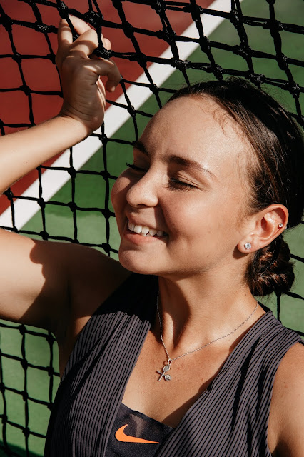 Happy woman with her eyes closed and leaning against a tennis net.