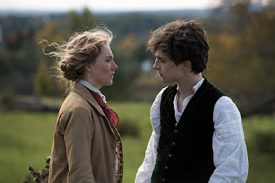"Jo March (Saoirse Ronan) and Theodore Laurence (Timothée Chalamet) stare into each other's eyes on a rolling hillside in a movie still for ""Little Women"" (2019)."